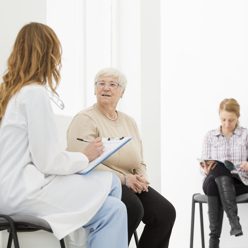 Doctor talking with senior female patient in waiting room
